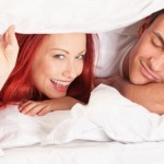 Cheerful young couple in bed